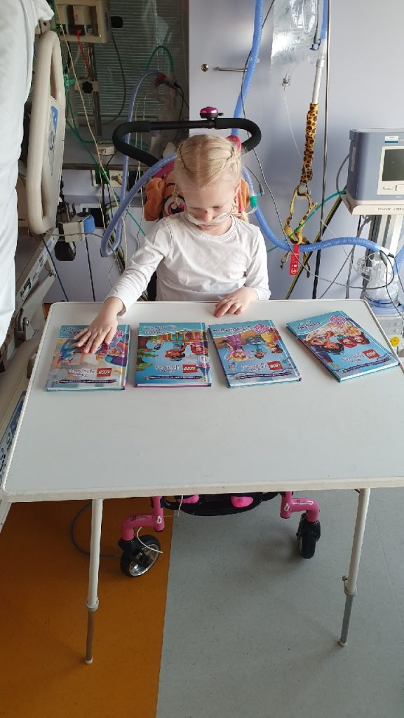 Nina in de stoel met boekjes.